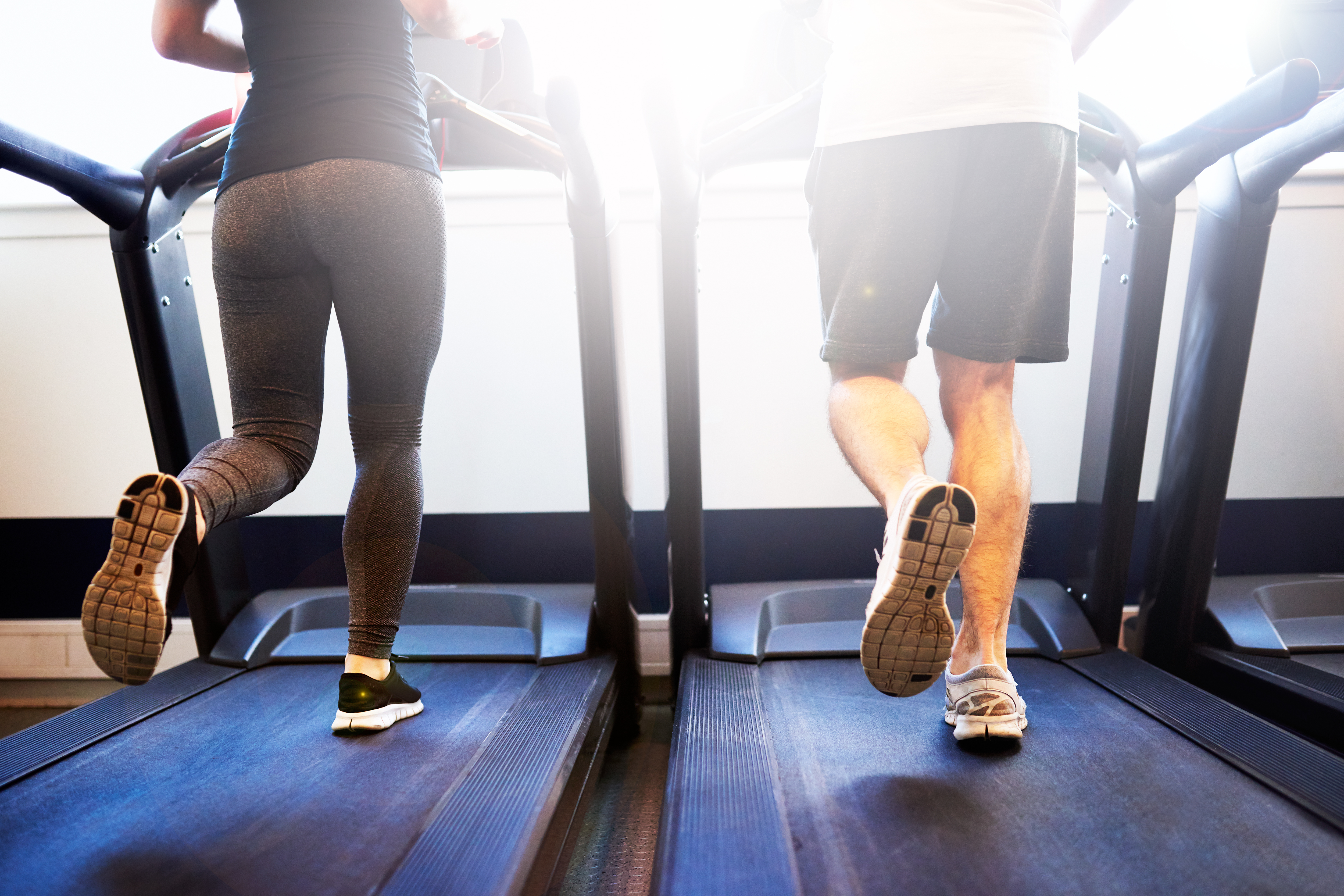 Male and female running on treadmills